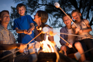 An image of a family roasting marshmallows over a flame.