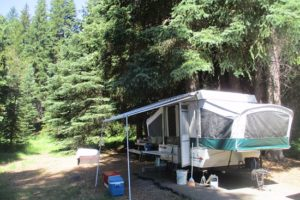 An image of a camp trailer set up among trees.