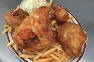 An image of a dinner plate with fried chicken, french fries and cole slaw.