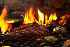 An image of a steak and artichokes over a flame. grill