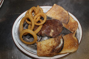 An image of a dinner plate with meat, toast and onion rings.