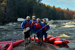 An image of 4 kayakers standing on a rock in the middle of the river.