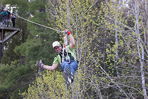 An image of a man zip lining through the trees.