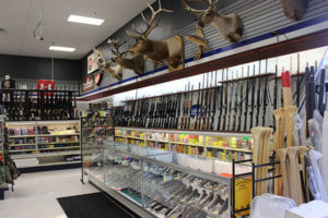 An image of a gun shop with game mounts on the wall.
