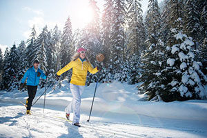An image of two people snow shoeing down a path in front of trees.
