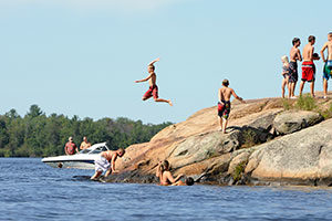 An image of boys jumping off rocks into the lake.