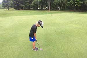 An image of a boy golfing.