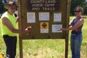 An image of a man and a woman in front of the Middle Inlet County Land Horse Camp and Trails sign.