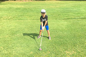 An image of a boy in his golf stance.