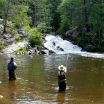 A picture of 2 people fly fishing in the water.