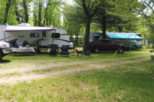 An image of a camp spot with a trailer and vehicles.