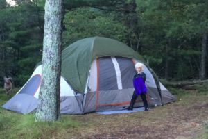 An image of a girl standing in front of a tent in the woods.