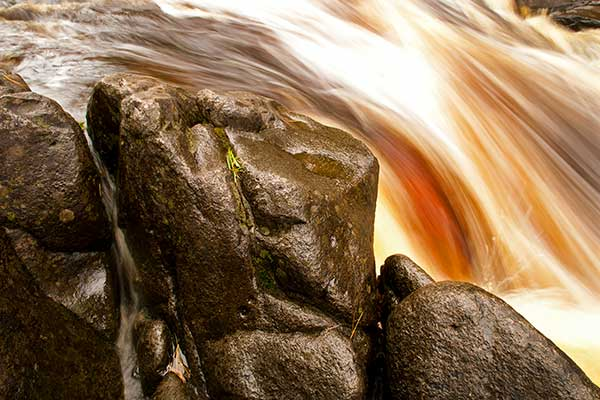 An image of a waterfall rushing over a rock.