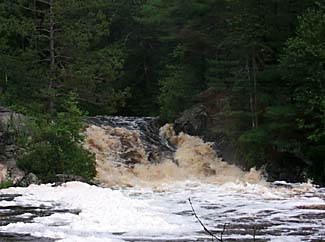 An image of rushing water falling over rocks into a river.