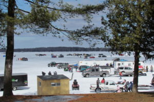 An image of several vehicles and people ice fishing.