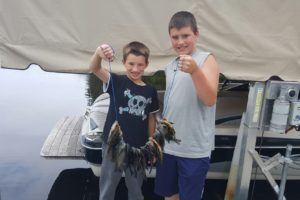 An image of 2 boys holding a stringer of fish.