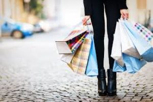 An image of the lower half of a woman, holding several shopping bags.