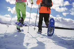 An image of the lower half of 2 people snow shoeing.