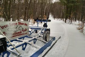A picture of a snow packed road leading through trees, with an Iron Snow Shoe Inc. Recreational Trail sign in front.