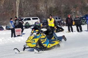 A picture of a snow mobile rider, with people watching behind him.