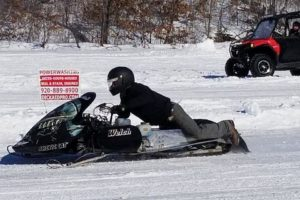 A picture of a man riding a snow mobile.