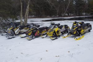 A picture of 4 snow mobiles in front of the water.