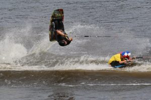 An image of a man flipping on a wake board, while 2 boys ride in the background.