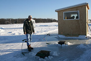 An image of a man ice fishing in front of a shack.